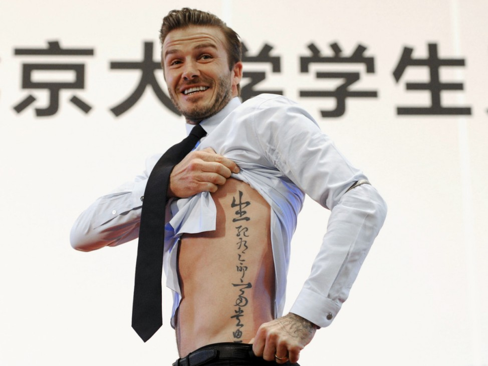 File photo of former England captain David Beckham showing his tattoo after he was asked to by students at Peking University during his visit in Beijing