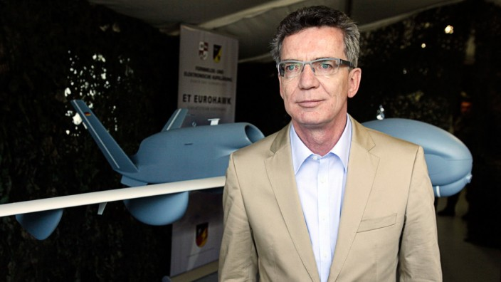 File picture shows German Defence Minister de Maiziere standing in front of a model of a 'EuroHawk' drone at Joint Support Service base in Grafschaft