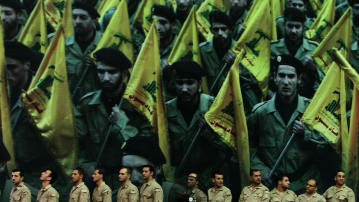 Musiker der Hisbollah vor einem Plakat mit Kämpfern