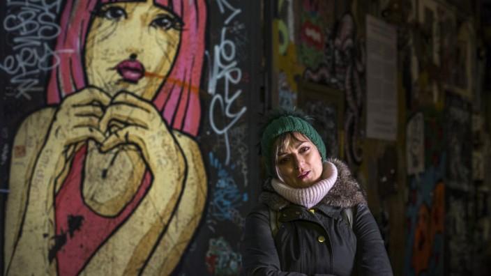 Die Griechin Evangelia Koika vor einem Graffiti in Berlin