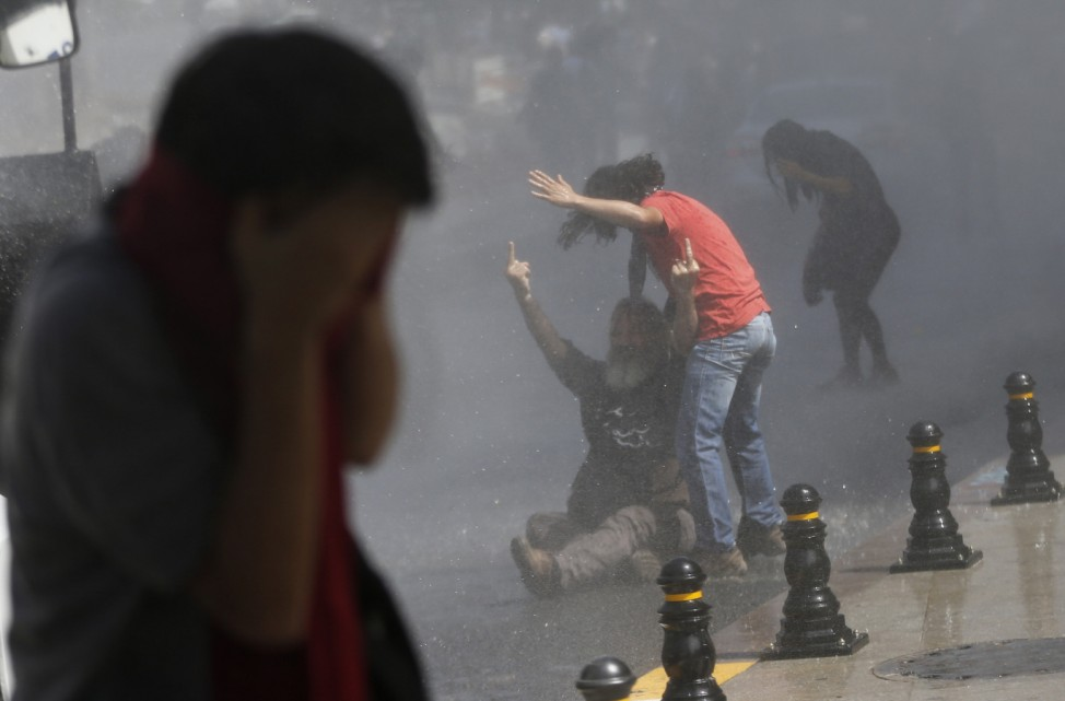 Demonstrator reacts as riot police use water cannon and tear gas to disperse crowd during protest against destruction of trees in park brought about by pedestrian project, in Taksim Square in central Istanbul