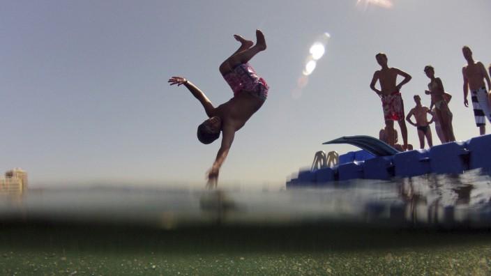 A boy dives into the water from a recreational platform at Magaluf beach, a popular tourist destination in Mallorca