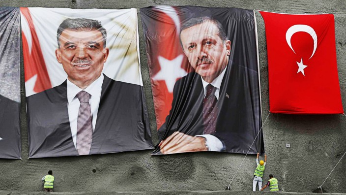 Workers hang portraits of modern Turkey's founder Ataturk, President Gul and PM Erdogan before a groundbreaking ceremony for the third Bosphorus bridge in Istanbul
