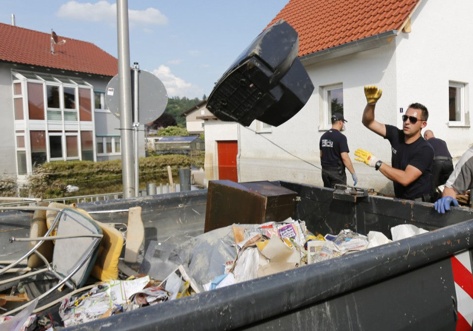 A Federal Police Bundespolizei officer throws a television into a rubbish dump after cleaning up debris caused by the subsiding Danube river floods in Fischerdorf
