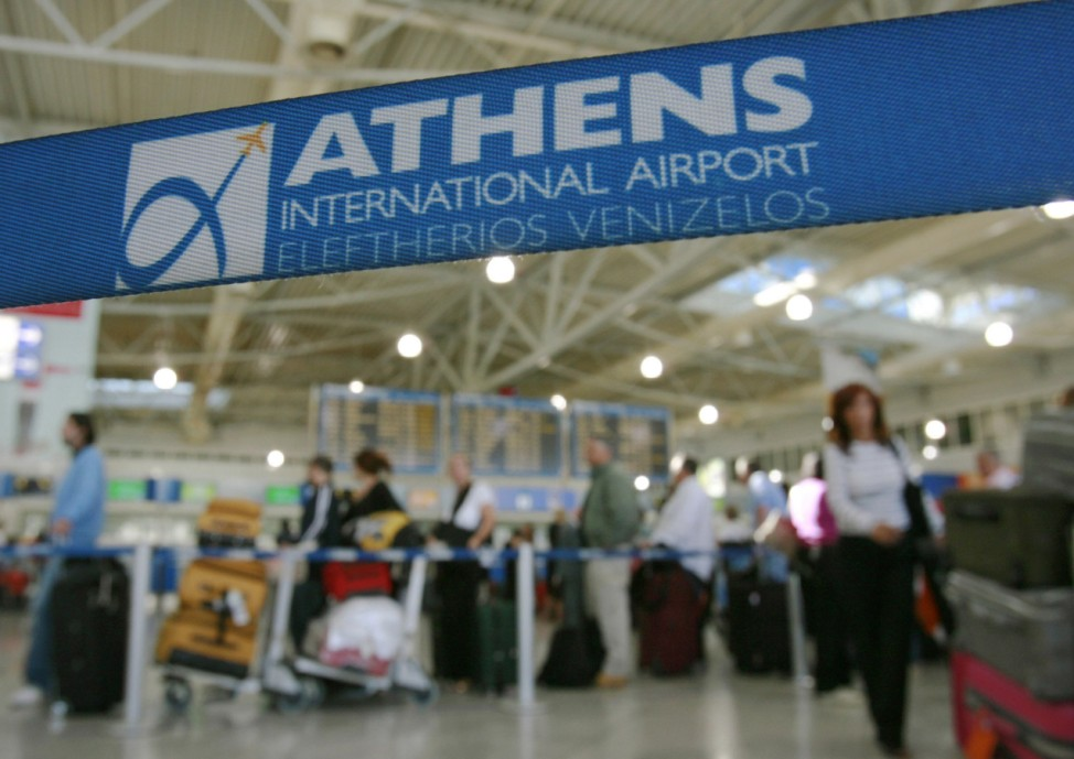 Passengers queue in front of check-in counters inside Athens airport
