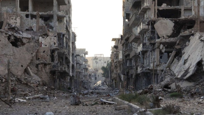 A general view shows damaged buildings and debris in Deir al-Zor