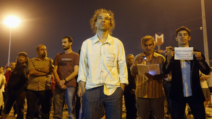 People stand during a silent protest at Taksim Square in Istanbul