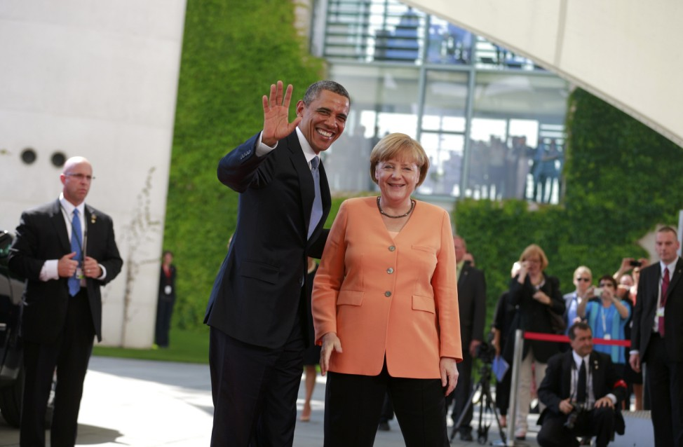 U.S. President Obama waves next to German Chancellor Merkel outside the Chancellery in Berlin
