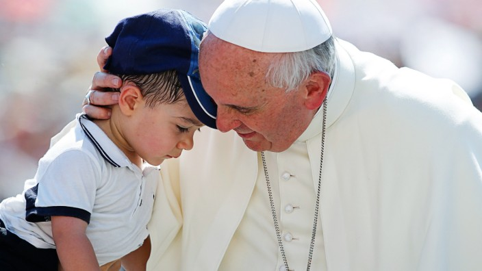 Pope Francis hugs a child as he arrives to lead the weekly audience in Saint Peter's Square at the Vatican