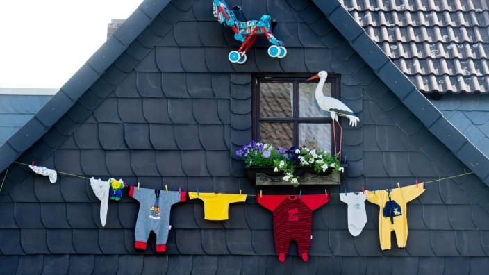 Babystrampler, ein Kinderwagen und ein künstlicher Klapperstorch in Ottbergen
