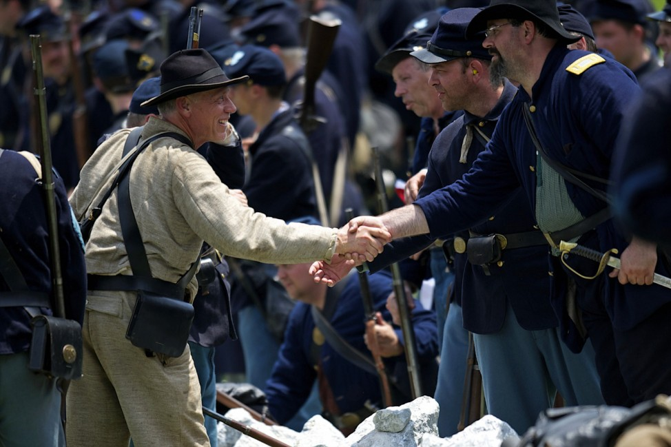 Actors playing Federal and Confederate troops shake hands after reenacting Battle of Gettysburg, in Gettysburg