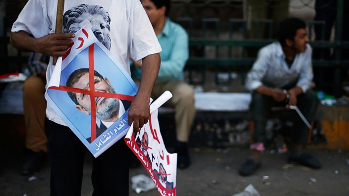 A protester opposing Egyptian President Mursi holds an anti-Mursi poster during a sit-in protest at Tahrir Square in Cairo