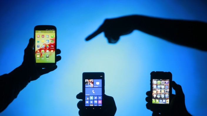 File photo of men posing with Samsung Galaxy S3 Nokia Lumia 820 and iPhone 4 smartphones in photo illustration in Zenica