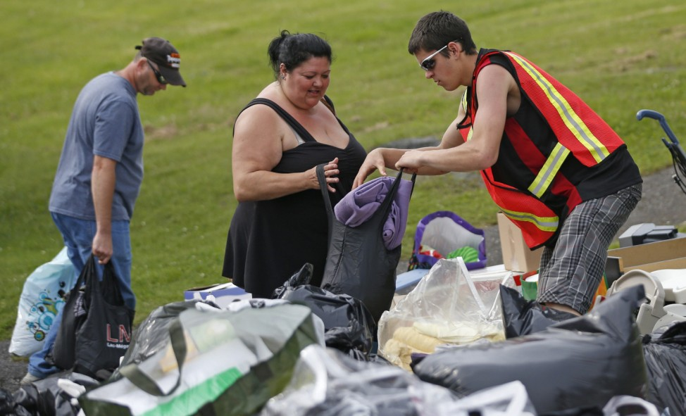 A volunteer gives clothes to a woman who's been evacuated from her home at the Polyvalente Montignac in Lac Megantic