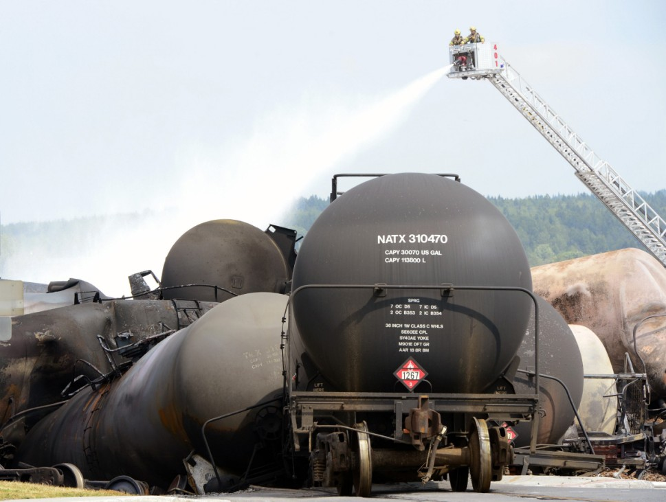 Firefighters spray water on the wreckage of the train explosion in Lac Megantic