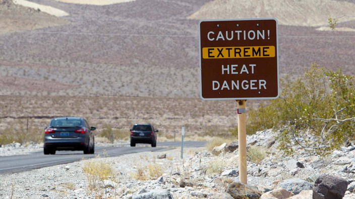 A sign warns of extreme heat as tourists enter Death Valley National Park in California