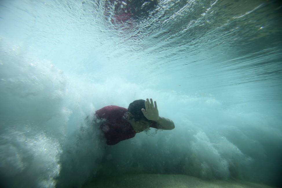A bodysurfer punches through a wave at the Ehukai sandbar near the surf break known as 'Pipeline' on the North Shore of Oahu, Hawaii.