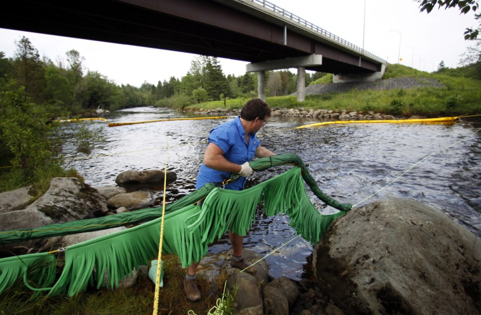 Scott Smith of Opflex Solutions places absorbent foam in the La Chaudiere River to collect crude oil in Lac-Megantic, Quebec