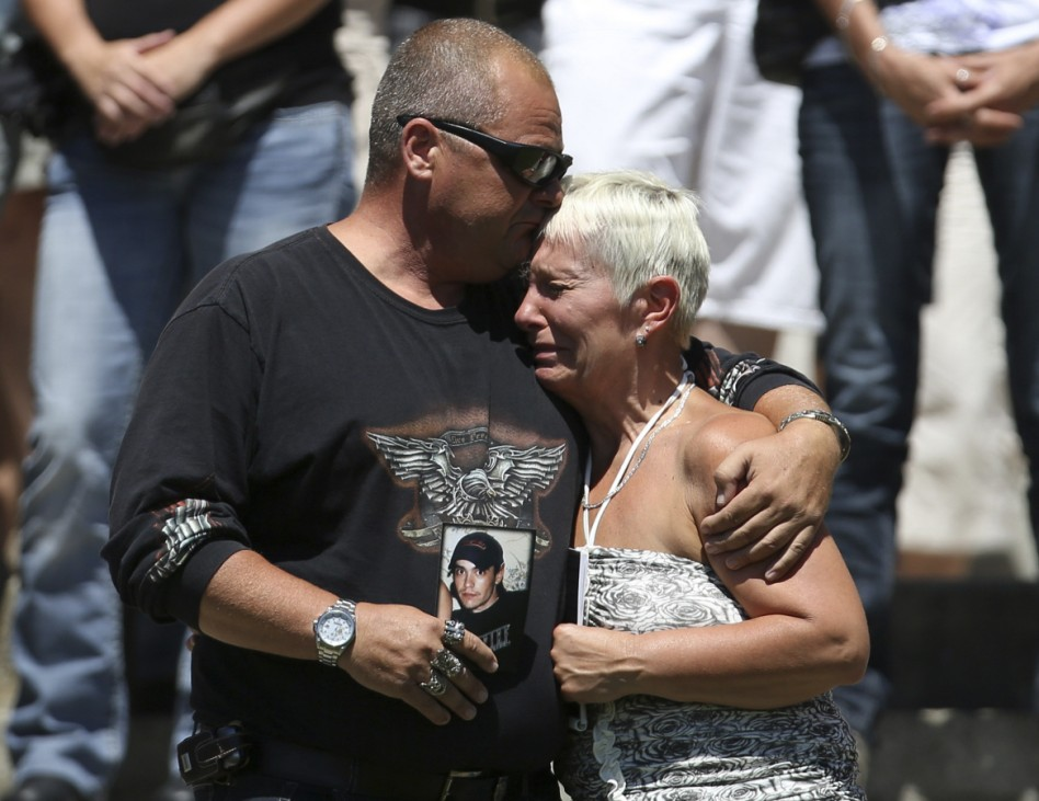 A couple mourns while the bells ring at the Sainte-Agnes church in Lac Megantic