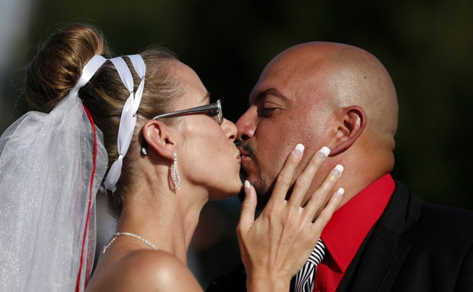 Newly-wed Manon Parise kisses her husband Marco Nunez near the site where a runaway train carrying crude oil exploded last week, in Lac-Megantic