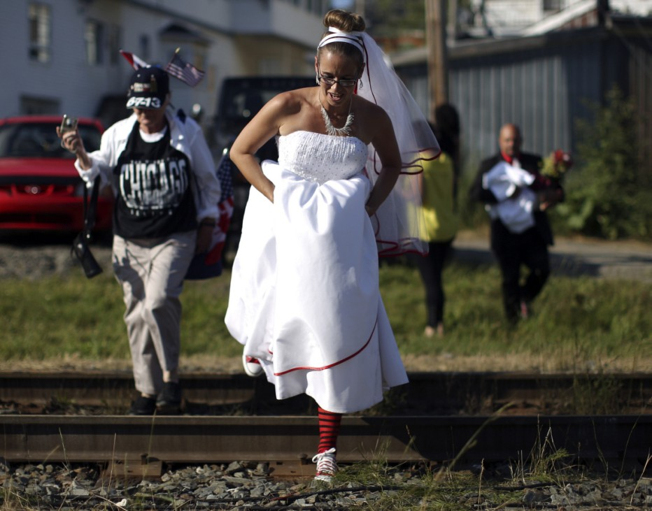 Newly-wed Parise steps over a railway track near the site where a runaway train carrying crude oil exploded last week, in Lac-Megantic