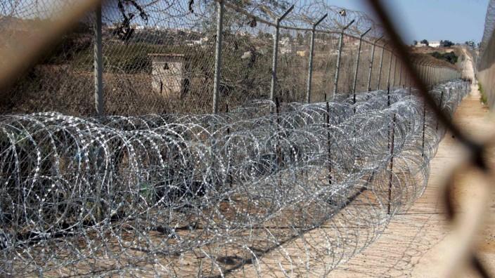 Stacheldraht-Barriere zwischen Grenzzäunen in Melilla