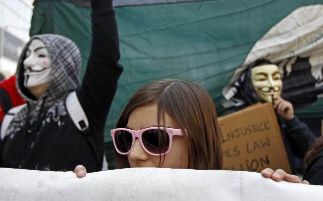 A girl and two protestors wearing masks of Guy Fawkes, march in Lisbon during the Portuguese general strike