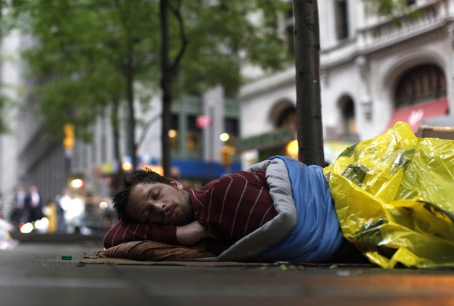 An Occupy Wall Street campaign protester sleeps on the sidewalk in Zuccotti Park