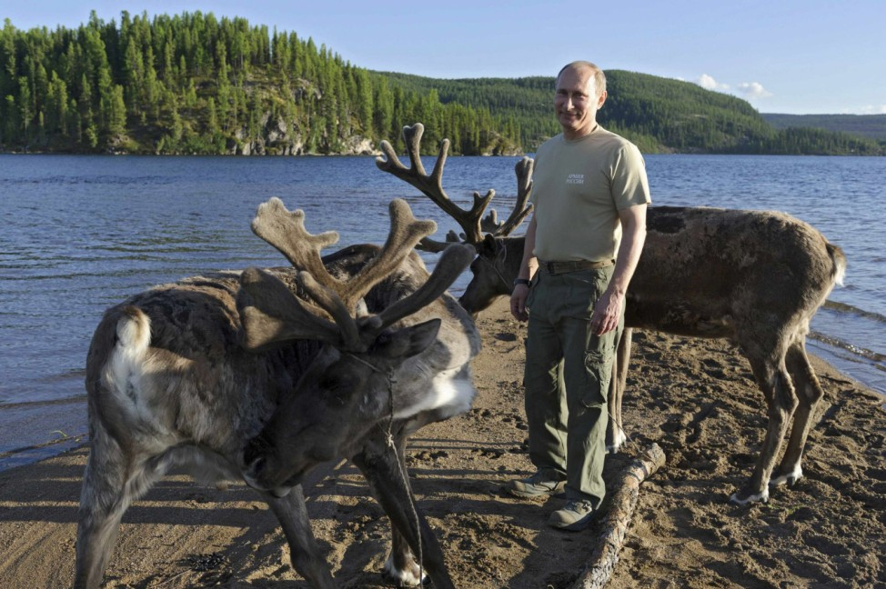 Russia's President Vladimir Putin poses for a picture beside reindeers in the Siberian Federal District