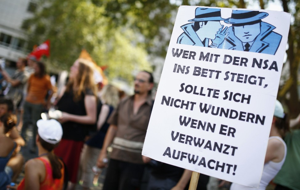 Protesters are seen behind placard during demonstration against NSA and in support of Snowden in Frankfurt