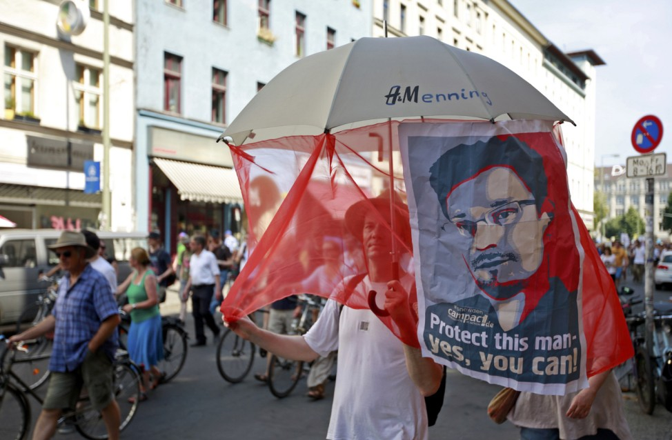 A protester marches with a portrait of Snowden during a demonstration against secret monitoring programmes PRISM, TEMPORA, INDECT and showing solidarity with whistleblowers Snowden, Manning and others in Berlin