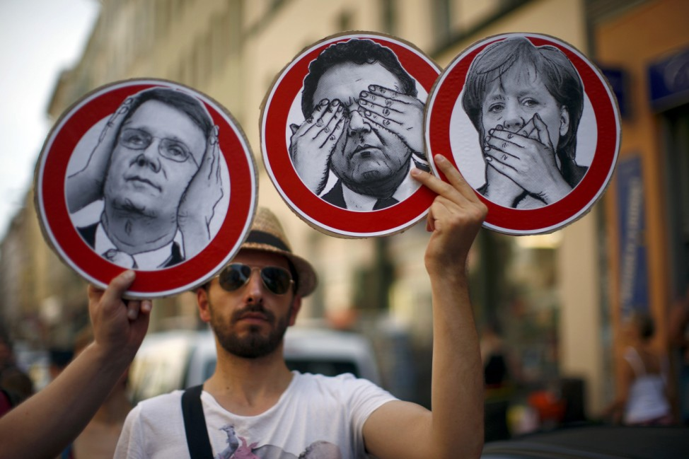 Protesters carry posters depicting German politicians, including Chancellor Merkel during a demonstration against secret monitoring programmes PRISM, TEMPORA, INDECT and showing solidarity with whistleblowers Snowden, Manning and others in Berlin