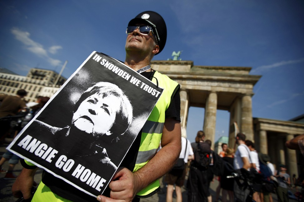 A protester holds a poster depicting German Chancellor Merkel as he attends a demonstration against secret monitoring programmes PRISM, TEMPORA, INDECT and showing solidarity with whistleblowers Snowden, Manning and others in Berlin