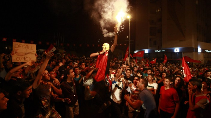 A demonstrator holds up a flare during a protest to demand the ouster of the Islamist-dominated government in Tunis