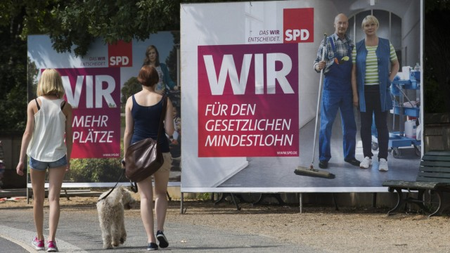 Women walk past election posters for Germany's upcoming general elections in Berlin