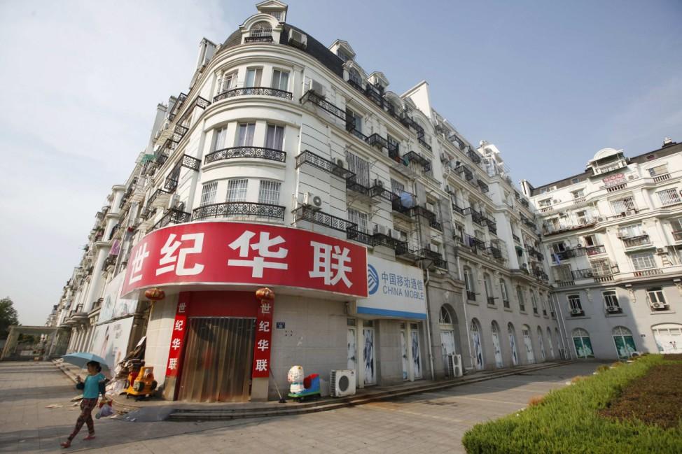 Woman walks past supermarket at Tianducheng development in Hangzhou