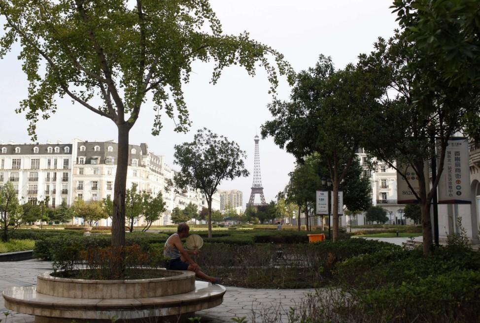 A man sits under a tree at the Tianducheng development in Hangzhou