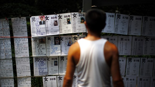 A man reads signs showing the personal profiles of people looking for spouses in People's Square in downtown Shanghai