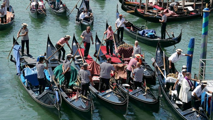 Priest standing in a gondola, and gondoliers pay their respects at the place near Rialto bridge where a German tourist was killed in Venice