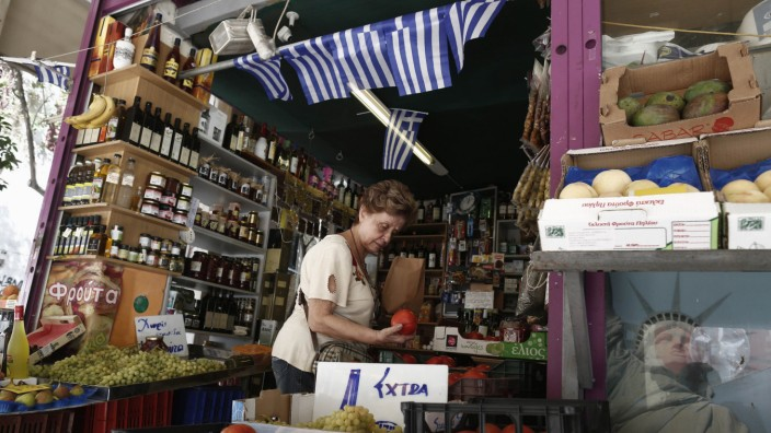 A woman buys tomatoes in a grocery market in central Athens