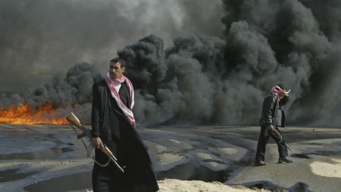 File photo of Iraqi policemen guarding the burning pipeline near the city of Kerbala