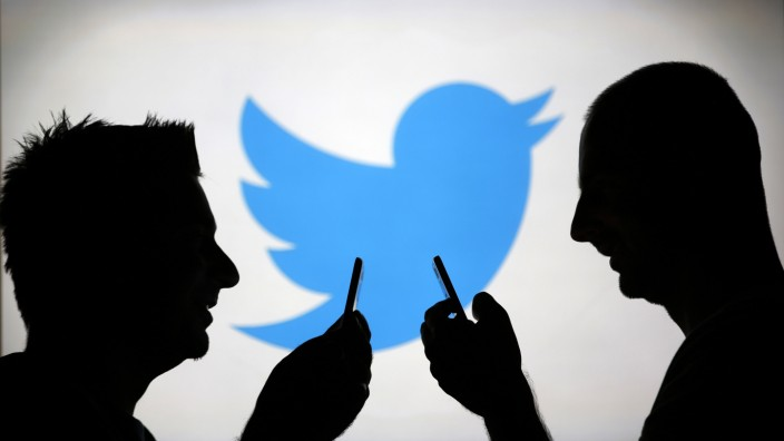 Men are silhouetted against a video screen with an Twitter logo as he poses with an Samsung S4 smartphone in this photo illustration taken in the central Bosnian town of Zenica