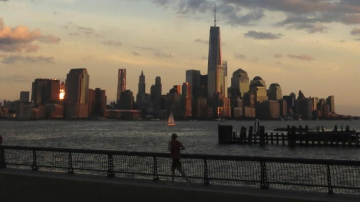 A man runs in front of the skyline of New York's Lower Manhattan and One World Trade Center in a park along the Hudson River in Hoboken