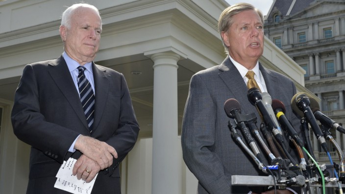U.S. Senator Graham  makes remarks to the media as U.S. Senator McCain listens, after meeting with U.S. President Obama at the White House in Washington