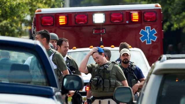 Heavily armed policemen walk from the Washington Navy Yard after a shooting in Washington