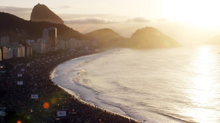 Pilgrims enjoy sunrise on Copacabana Beach ahead of Pope Francis' Sunday mass in Rio de Janeiro