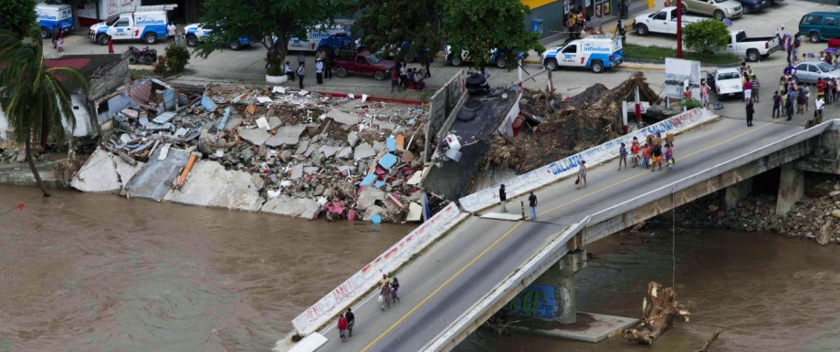 An aerial view shows people walking on a collapsed bridge in Acapulco