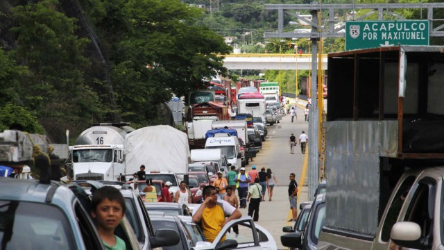 Tourists are caught in a traffic jam as cars line up to leave the city after the highway was reopened in Acapulco