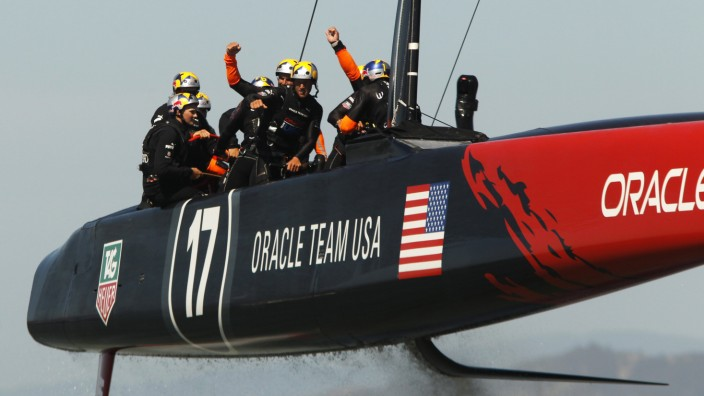 Crew members of Oracle Team USA react after defeating Emirates Team New Zealand during Race 18 of the 34th America's Cup yacht sailing race in San Francisco, California