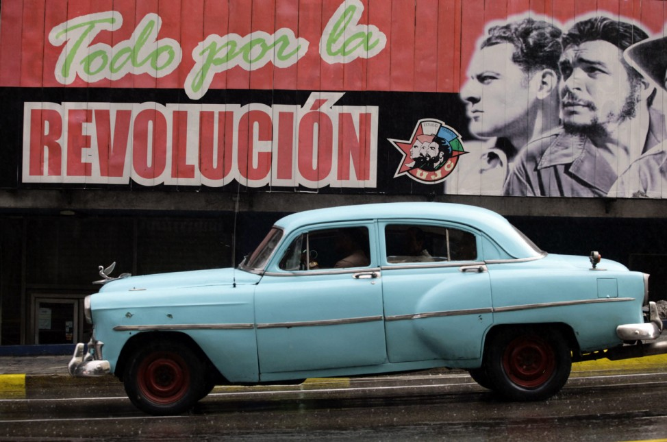 A U.S.-made car, used as a private collective taxi is driven beside a billboard in Havana